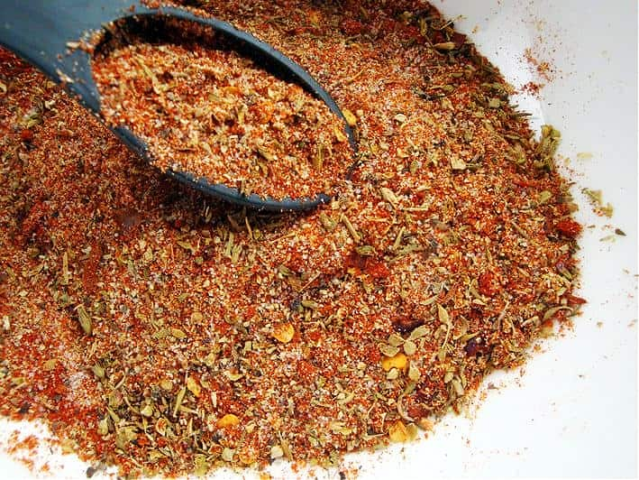 cajun spice mix with tablespoon in white bowl