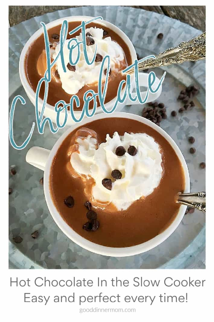 """two white cups of hot chocolate with whipped cream and chocolate chips on top. Words """"hot chocolate"""" appear over top of photo"""