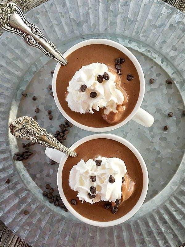 two cups hot chocolate in white cups on silver plate with whipped cream and chocolate chips on top