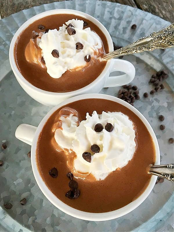 two cups hot chocolate with whipped cream and chocolate chips on top. On silver plate