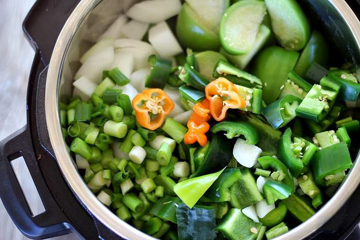 close up of veggies in the instant pot before cooking. peppers, onions, tomatillos, habenaros, green onions.