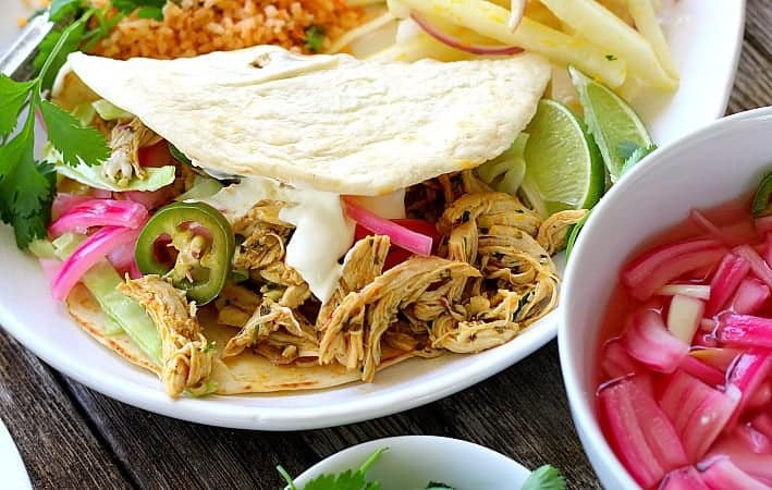 chicken tacos on white plate with pickled red onion on side