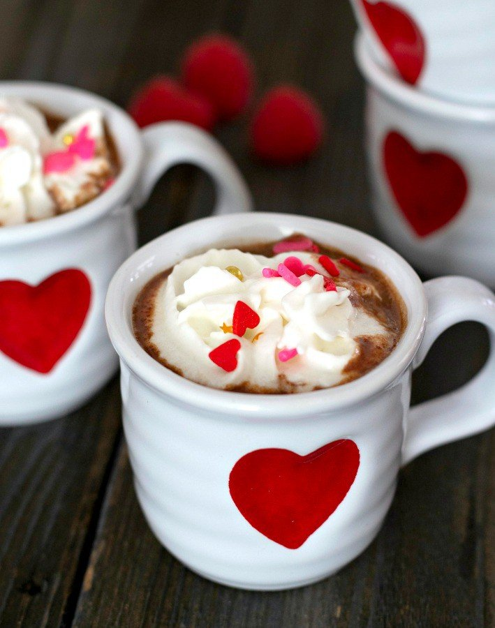 hot chocolate with raspberry puree mixed in it. in tiny white mugs with red hearts on them. whipped cream and red heart sprinkles