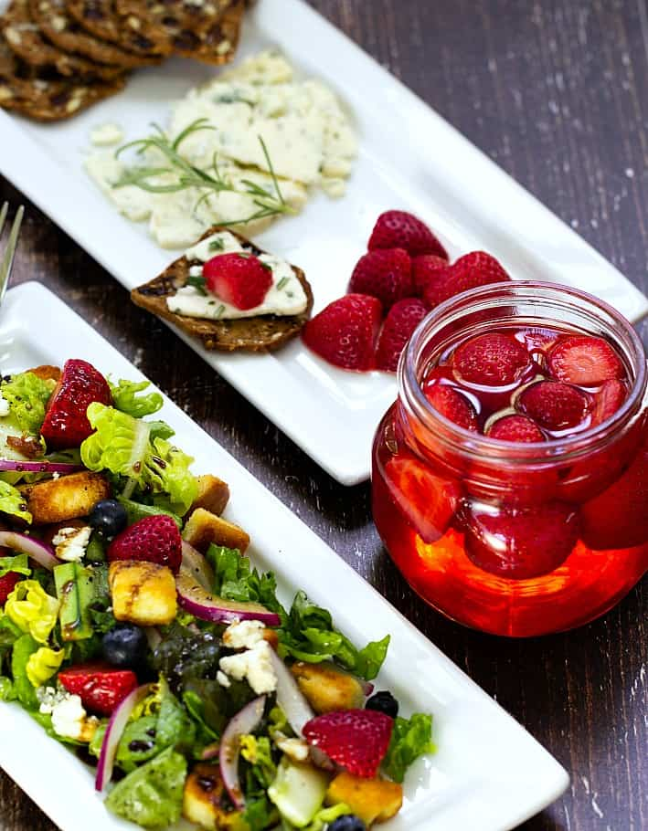 pickled strawberries on cheese and in salad on a plate