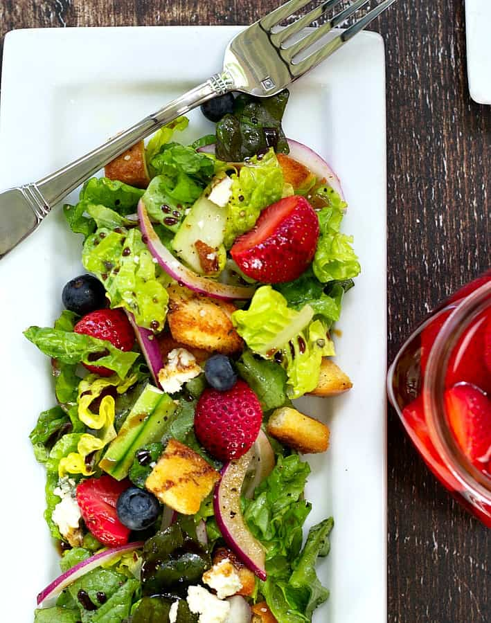 pickled strawberries in a tossed green salad
