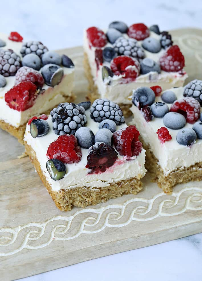 Easy cheesecake bars with frozen berries on top on a serving tray