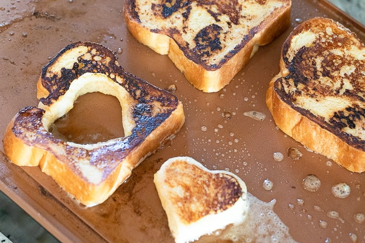 Bread for French Toast cooking on griddle. One piece has heart shaped hole cut out for Egg In the Hole