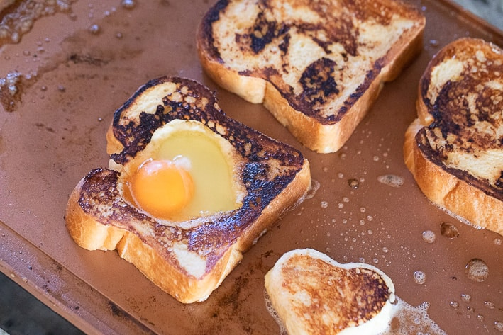 Egg in the hole and regular pieces of bread toasting on a griddle