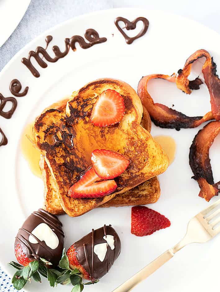 French toast on a white plate with heart shaped bacon, chocolate covered strawberries and Be Mine written in chocolate