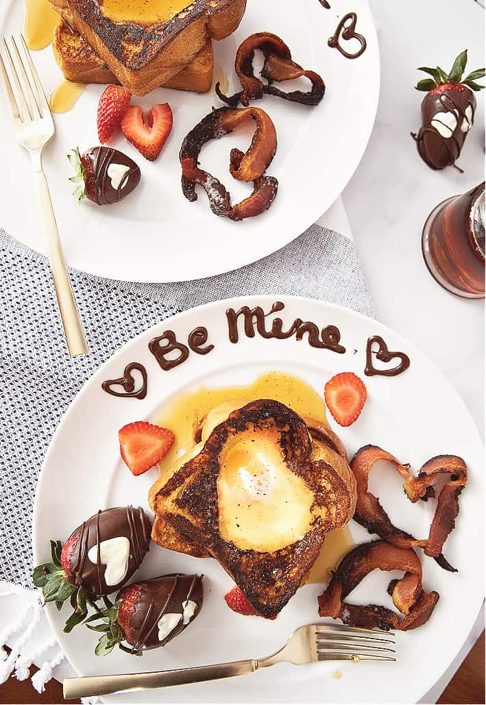 Two plates of Egg In The Hole French toast with heart shaped bacon, chocolate covered strawberries, white chocolate hearts on the strawberries, Be Mine is written on the plates