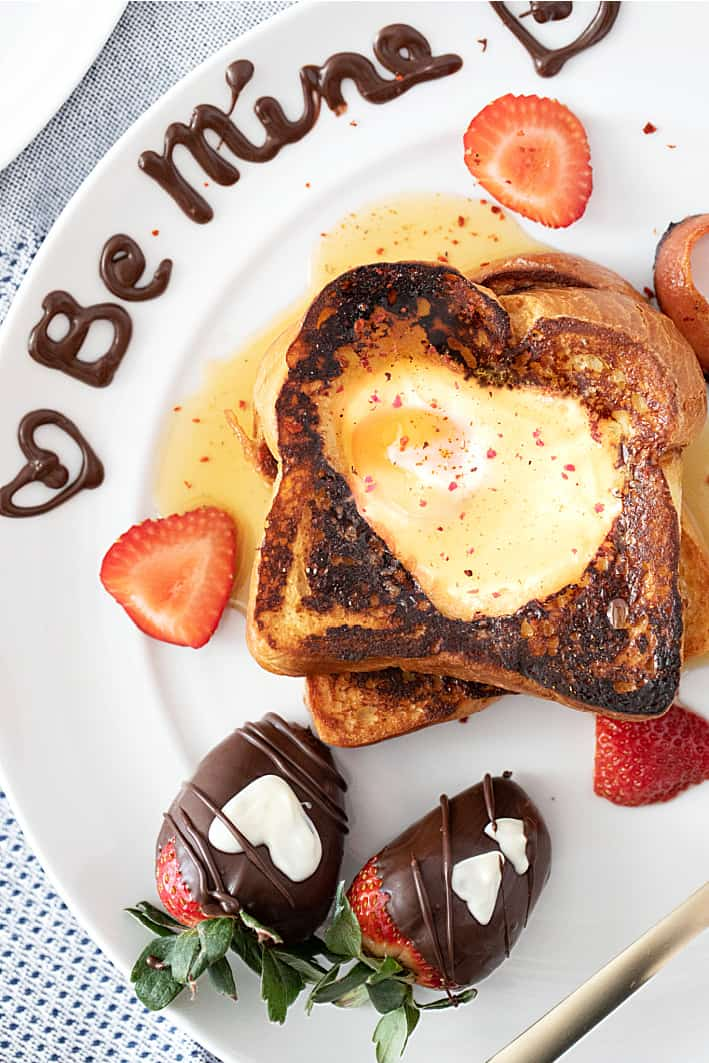 Egg In The Hole French toast on a white plate with chocolate dipped strawberries and Be Mine written in chocolate