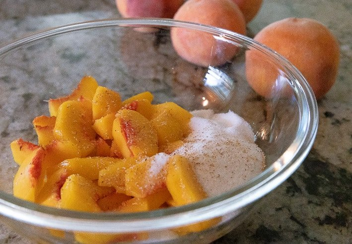 peaches and sugar and nutmeg in a bowl with fresh peaches next to the bowl