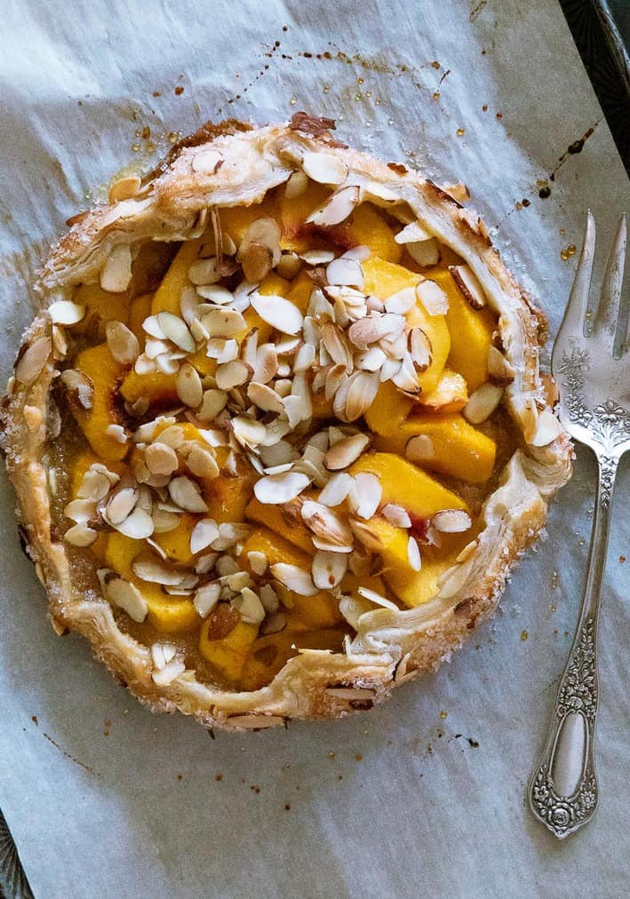 peach puff pastry tart with almonds on parchment lined baking sheet with fork on the right of the tart