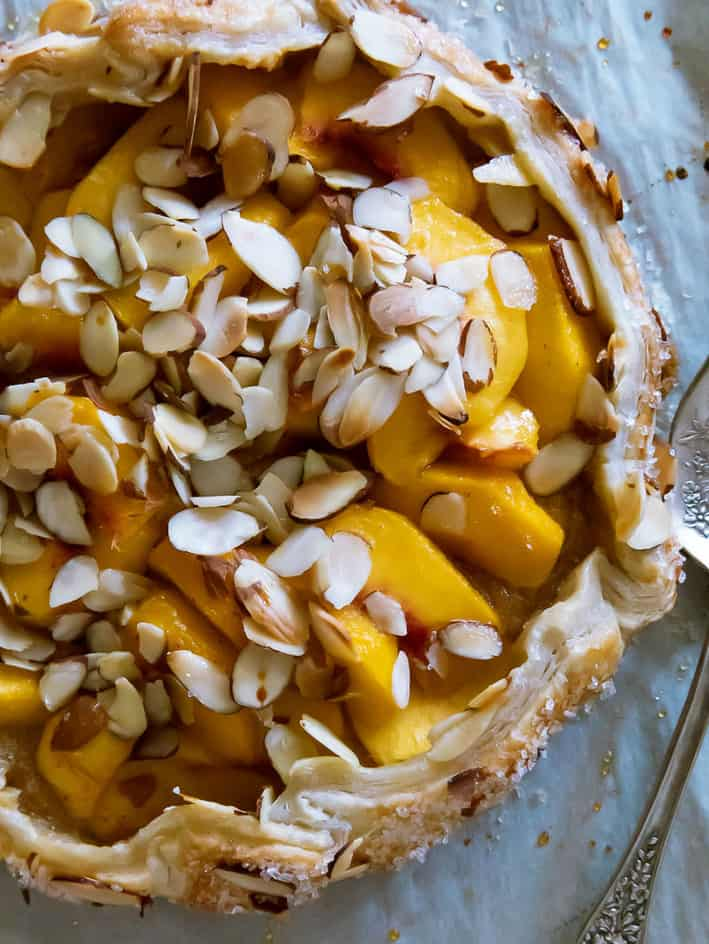 Close up photo of peach puff pastry tart with almonds on top. Fork to the right