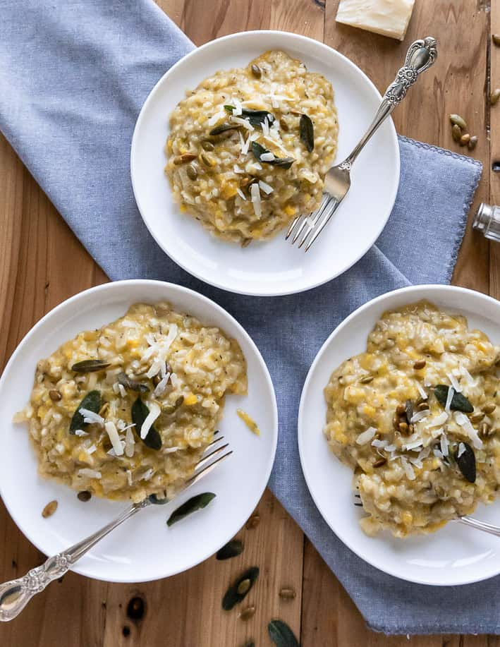 three white plates with pumpkin risotto and sage leaves on a wood background with blue napkin