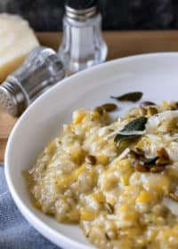 pumpkin risotto in white dish with salt and pepper shakers at top. crisp sage leaves and pumpkin seeds on risotto