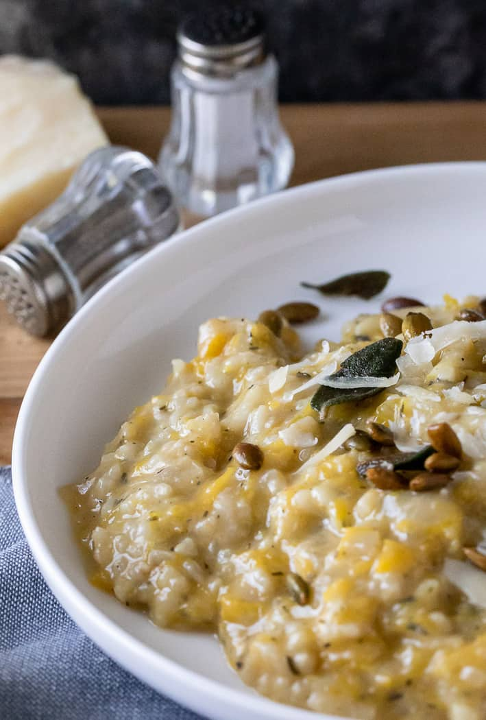 dish of pumpkin risotto with salt and pepper shakers and chunk of parmesan in background. crisp sage leaves and pumpkin seeds on top