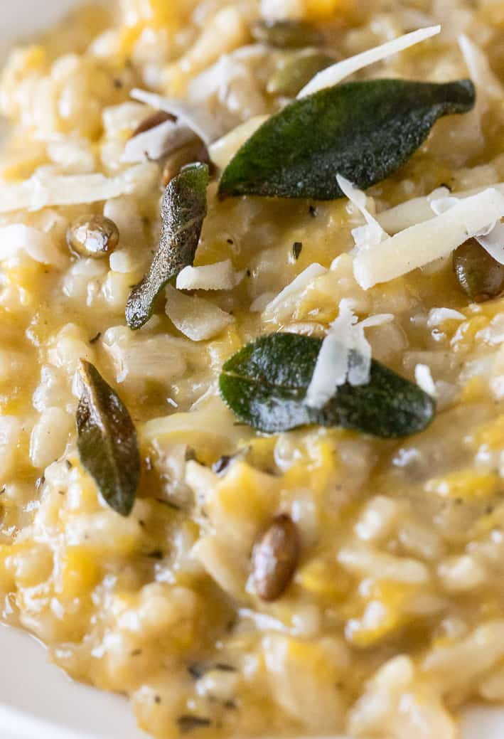 closeup of pumpkin risotto with crisp sage leaves and pumpkin seeds and parmesan