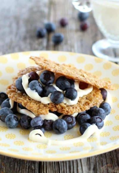oatmeal crisps stacked on a yellow plate with blueberries and creme fraiche