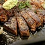 Porterhouse Steak in cast iron skillet with herbed butter