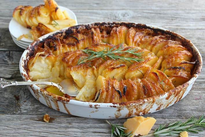 Scalloped potatoes in a white shallow bowl