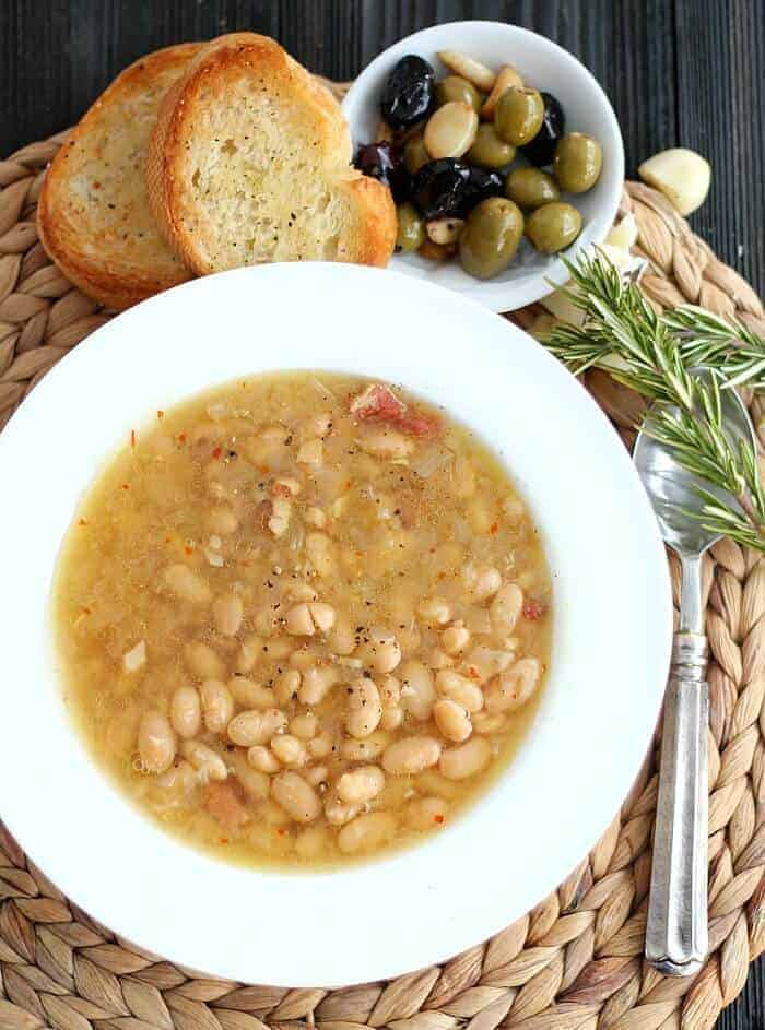 Tuscan White Bean Soup in white bowl. Bowl of olives and crusty bread above white bowl