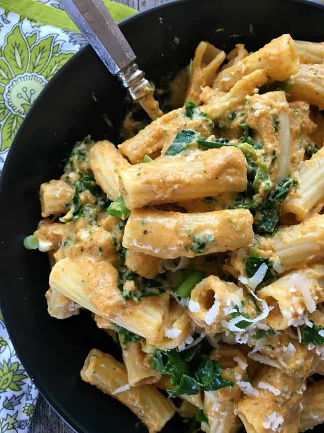 close up of pumpkin alfredo pasta in a bowl with a fork