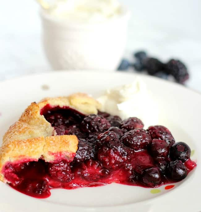 berry galette after cut into serving slice on a white plate with whipped cream on the side