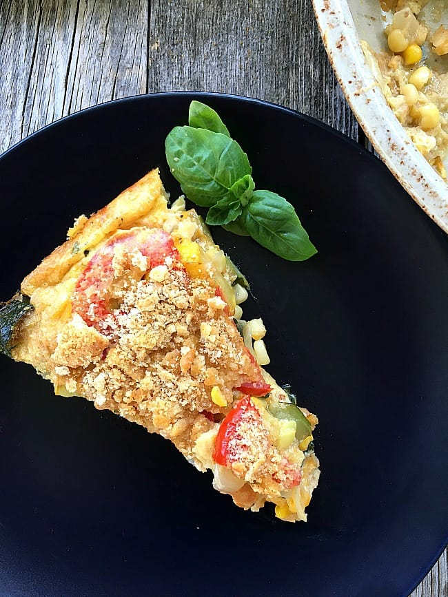 Zucchini and Summer Squash Casserole is baked with fresh basil, roma tomatoes and sweet corn. An excellent side dish or tasty vegetarian main course.
