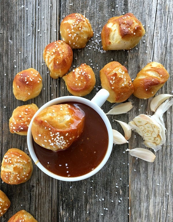 Homemade Pretzel Bites and Garlic Caramel Sauce on a wooden board with garlic cloves