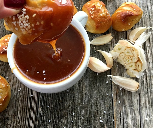 homemade pretzels being dipped in sauce and garlic cloves on a wooden board